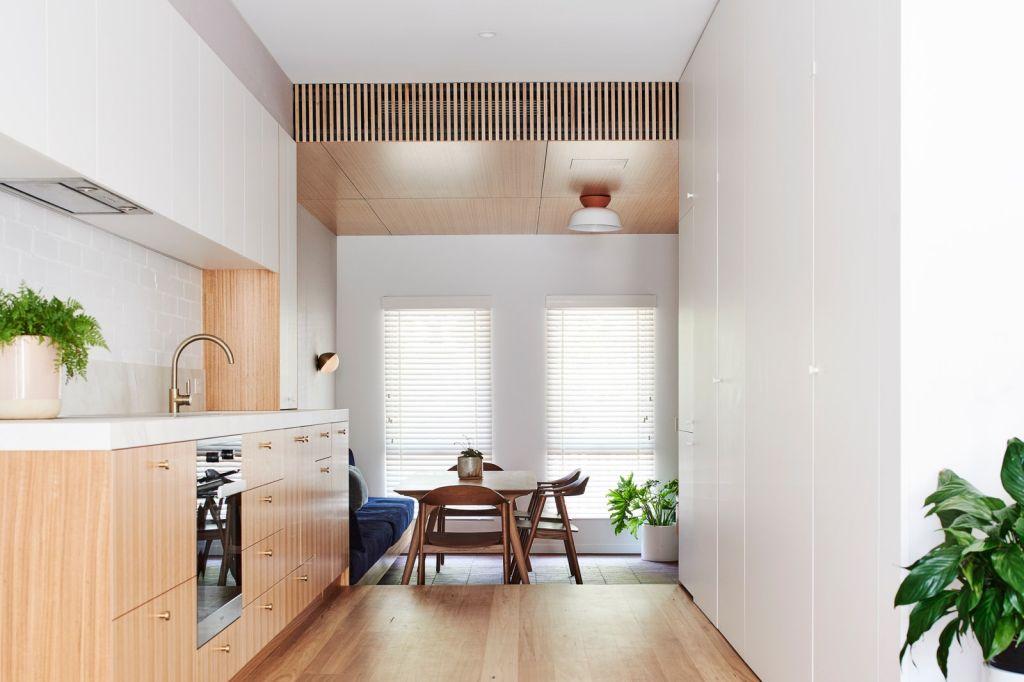 Bancada da cozinha à esquerda, à direita armários de chão ao teto branco, e ao fundo, alguns degraus abaixo, a sala de jantar, e entrada da casa.