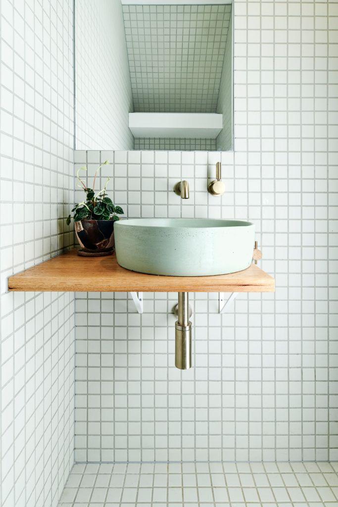 Parede com ladrilhos branco, pia suspensa com apoio de madeira, cuba redonda e metais em dourado. Do lado esquerdo da cuba, um vaso pequeno. Acima, um espelho quadrado