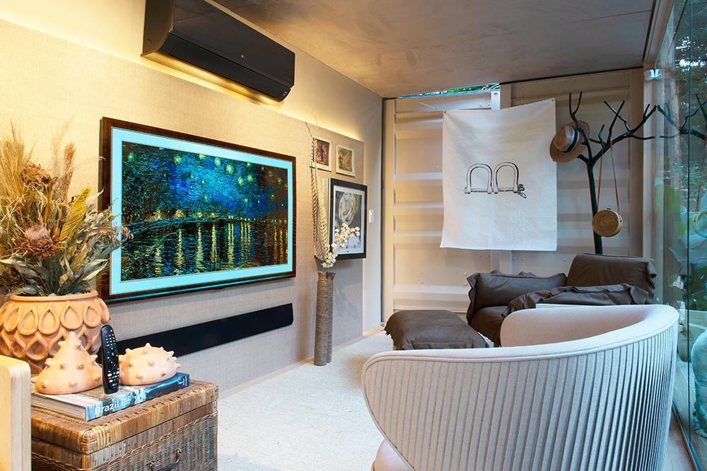 Sala de tv com duas poltronas. Na tv, imagem de pintura de Van Gogh