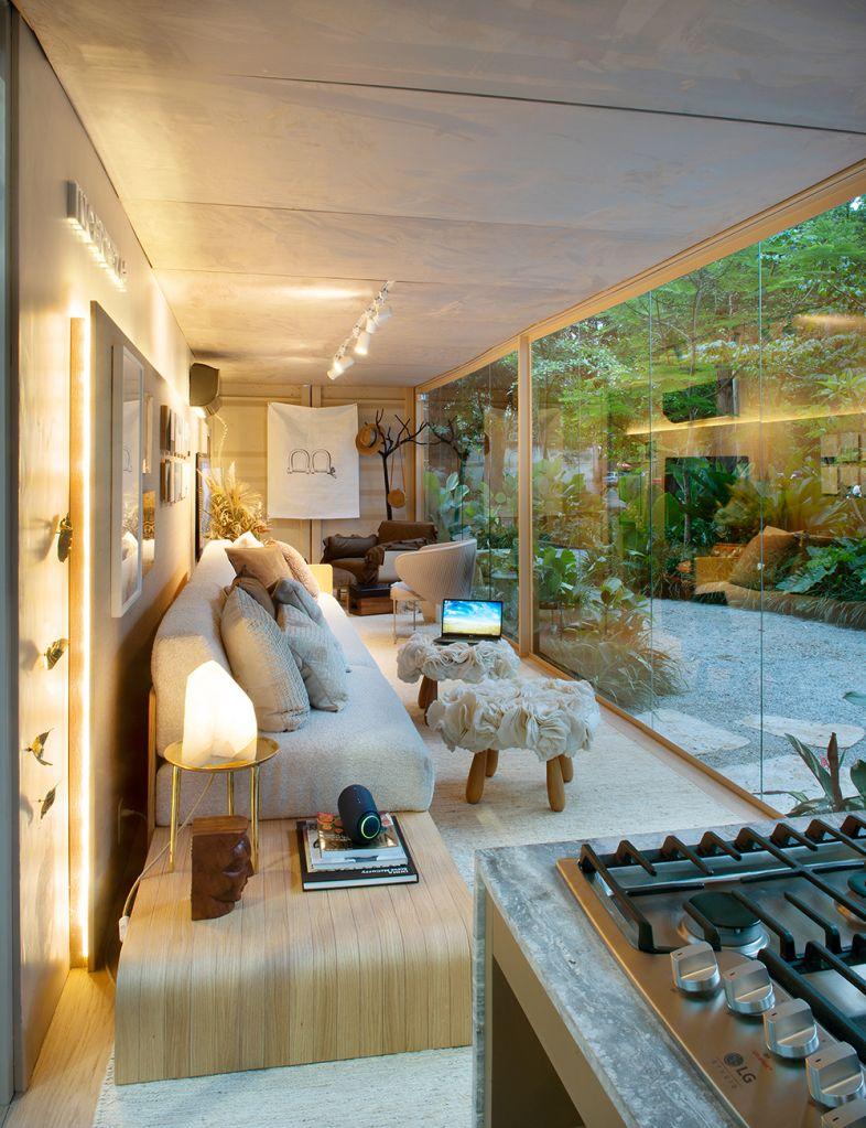 Living com mesa lateral, painel iluminado, sofá e banquinhos de apoio; à frente a parede de vidro do contêiner