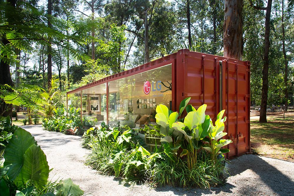 Contêiner vermelho visto do lado de fora, envolto por jardim, com logo da LG aparente.