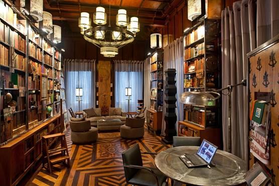 Biblioteca com piso em madeira. Sofá, mesa, duas poltronas e cadeira