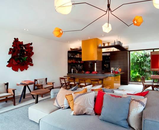 Living com sofás e almofadas. Lustre em primeiro plano