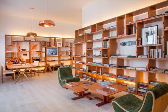 Biblioteca com duas poltronas verdes e estantes vazadas de madeira