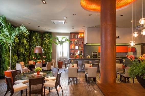 Restaurante com parede verde. Mesas e cadeiras