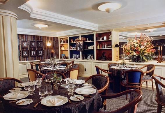 Restaurante com estantes nas paredes. Mesas e arranjos de flores