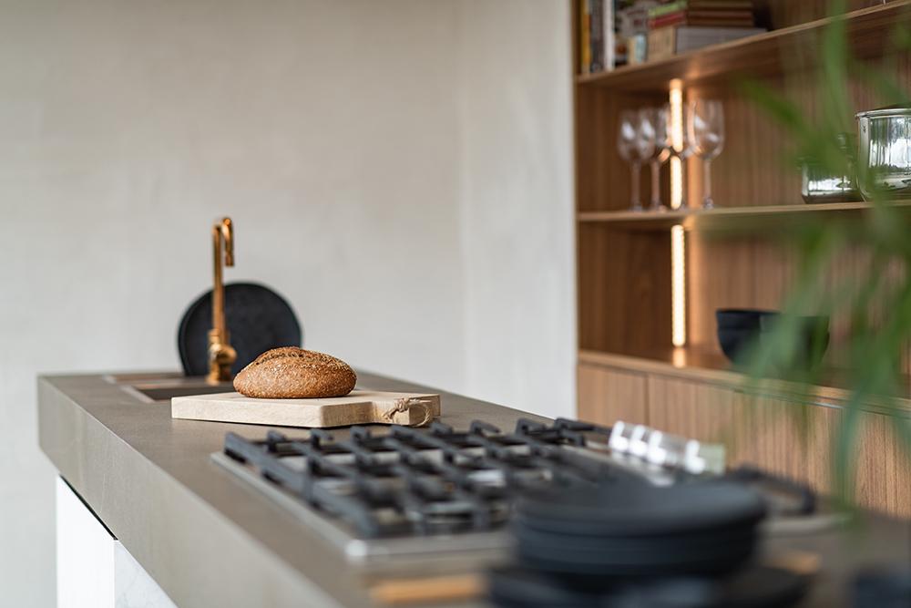 Detalhe na bancada com cooktop e uma tábua de madeira com um pão