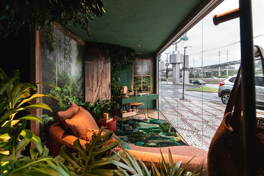Imagem do home office com sofá laranja e mesa verde