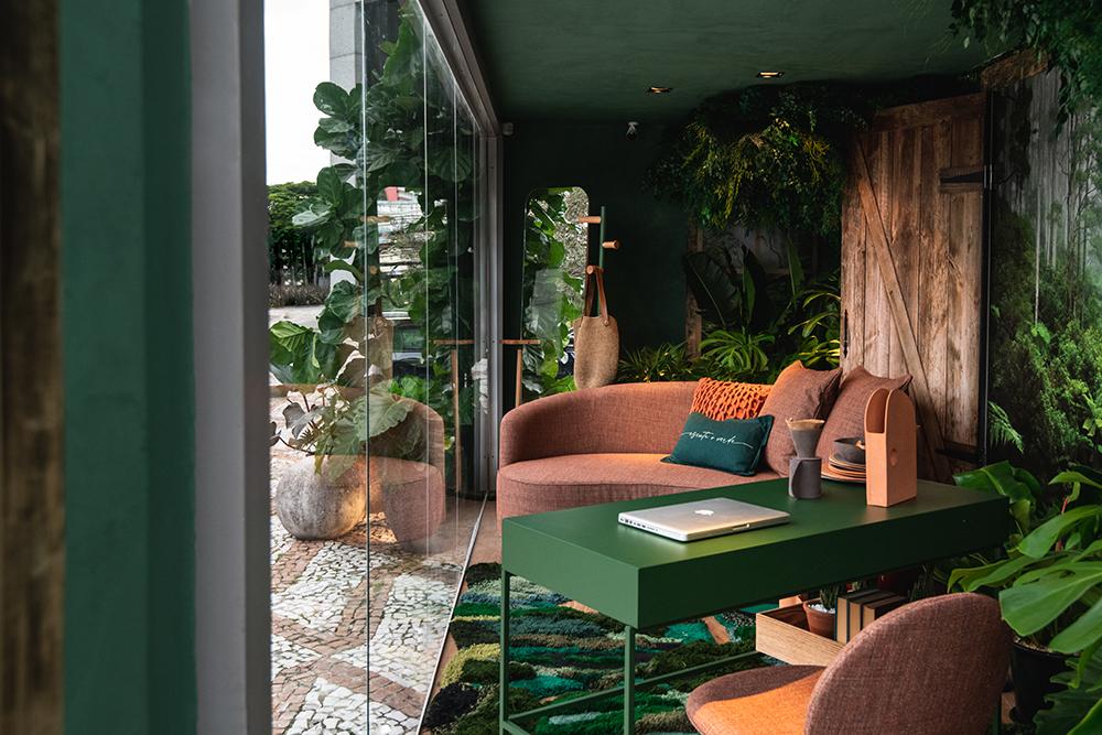 Living com mesa verde e sofá laranja. Muitas plantas ao redor