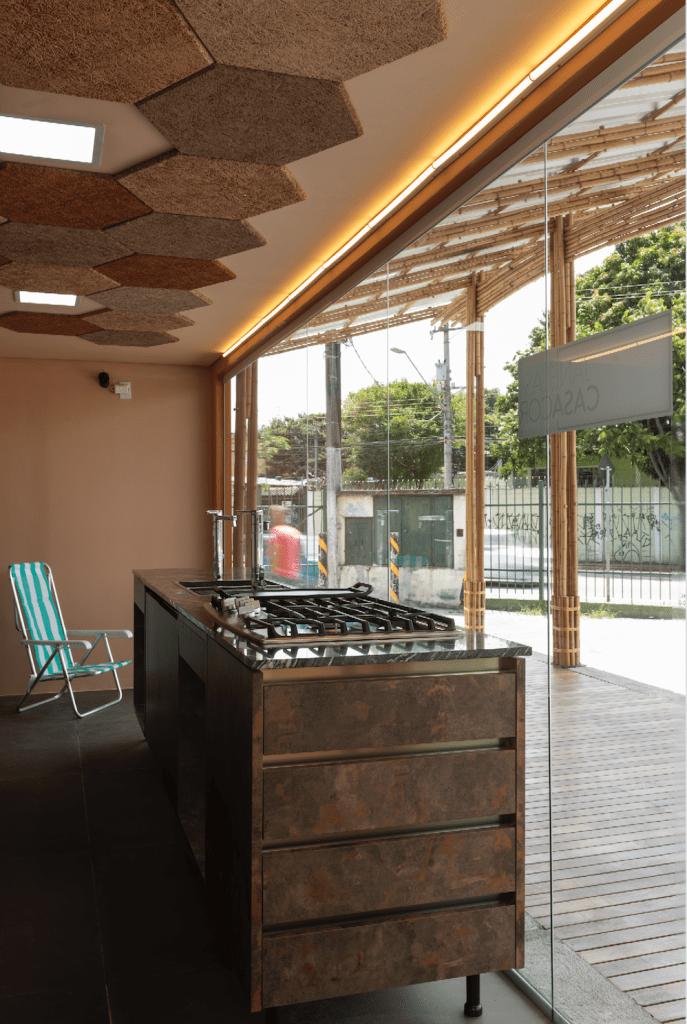Parte interna da cozinha comunitária, com a bancada em tom de ferrugem, com um cooktop e torneira. Ao fundo, uma cadeira de praia com listras azuis e brancas. No teto, peças hexagonais e na parede marrom avermelhado. Do lado de fora, atrás do vidro do conteiner, um deck de piso de madeira, e cobertura feira com estrutura de bambu.