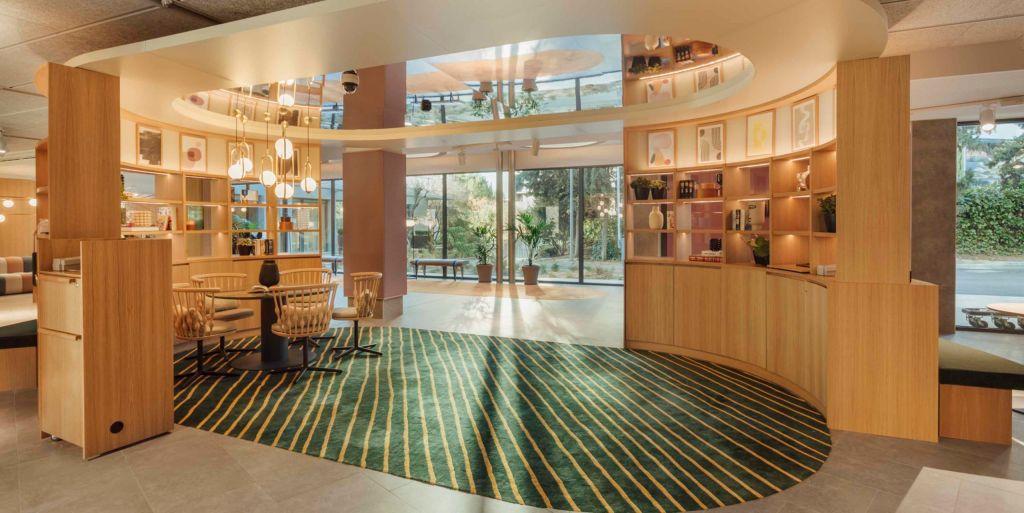 Lobby com tapete verde e listras amarelas. Ele é emoldurado por armários de madeira clara