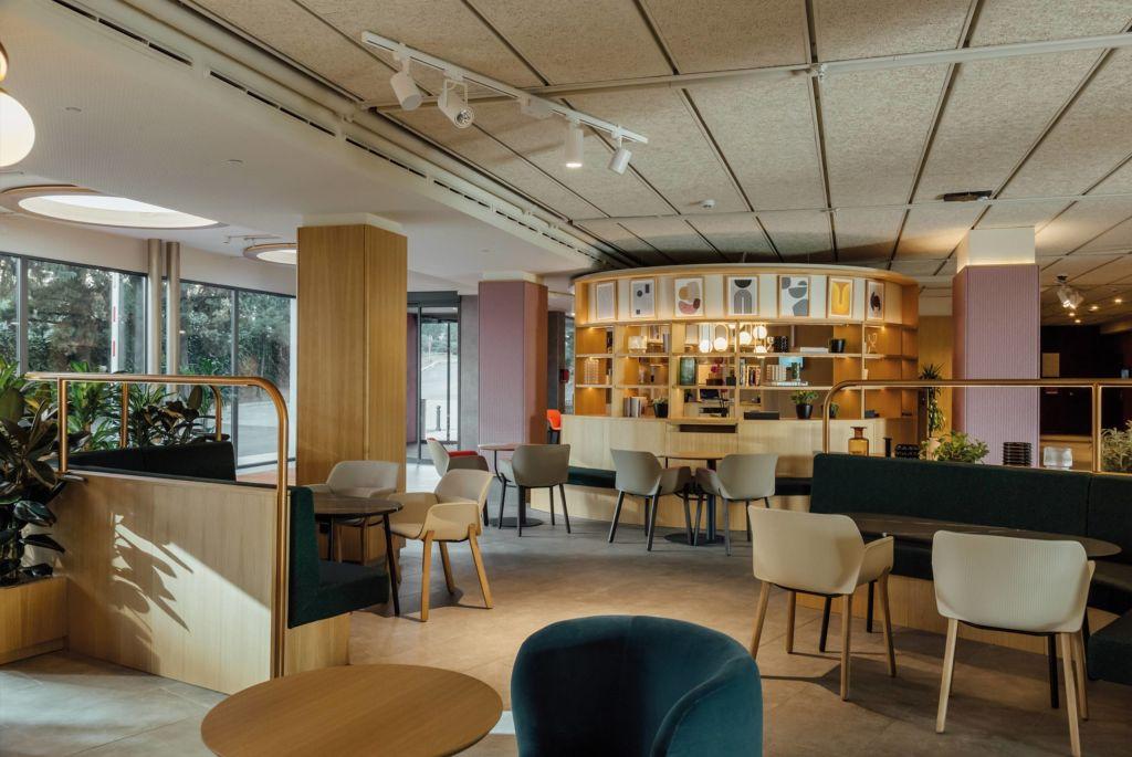 Restaurante com mesas e cadeiras acolchoadas. Estante em madeira ao fundo