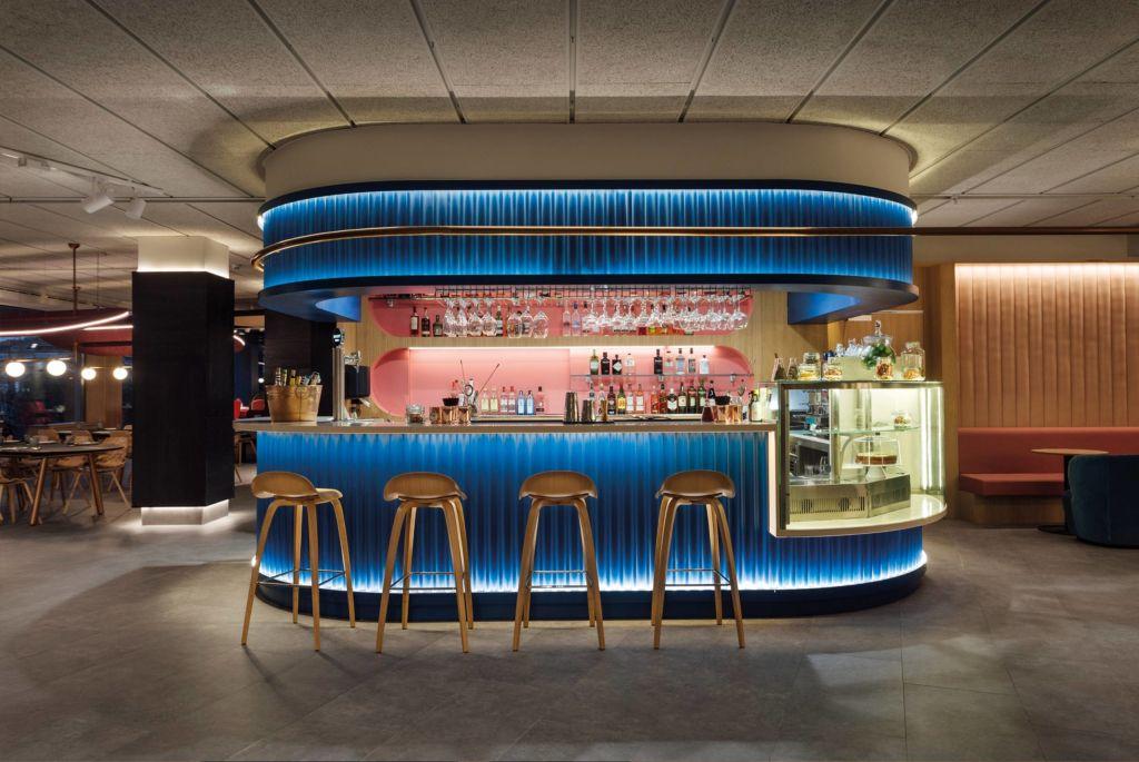Bar com bancada azul iluminada e bancos altos de madeira