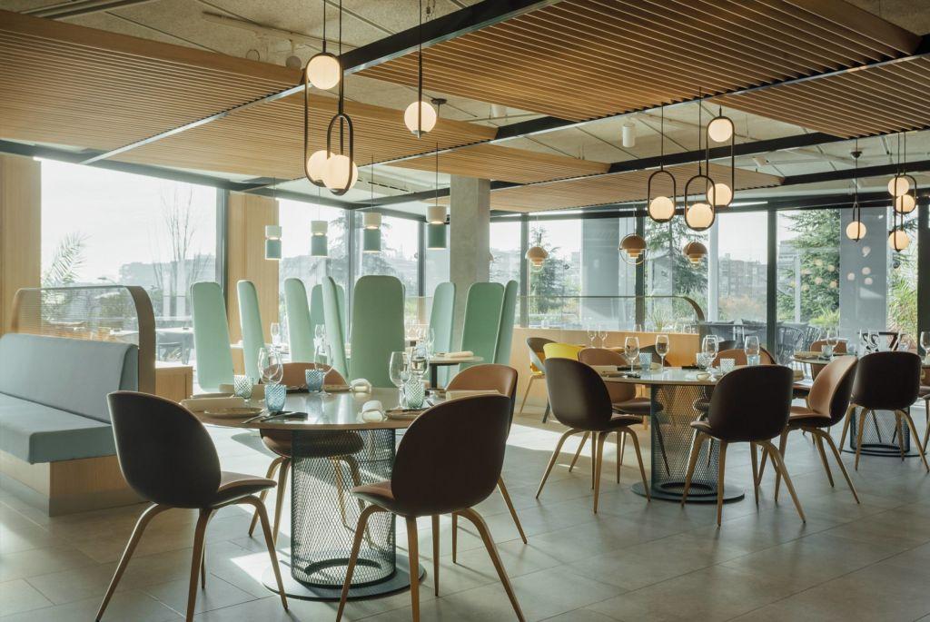 Restaurante com mesas circulares e luminárias esféricas