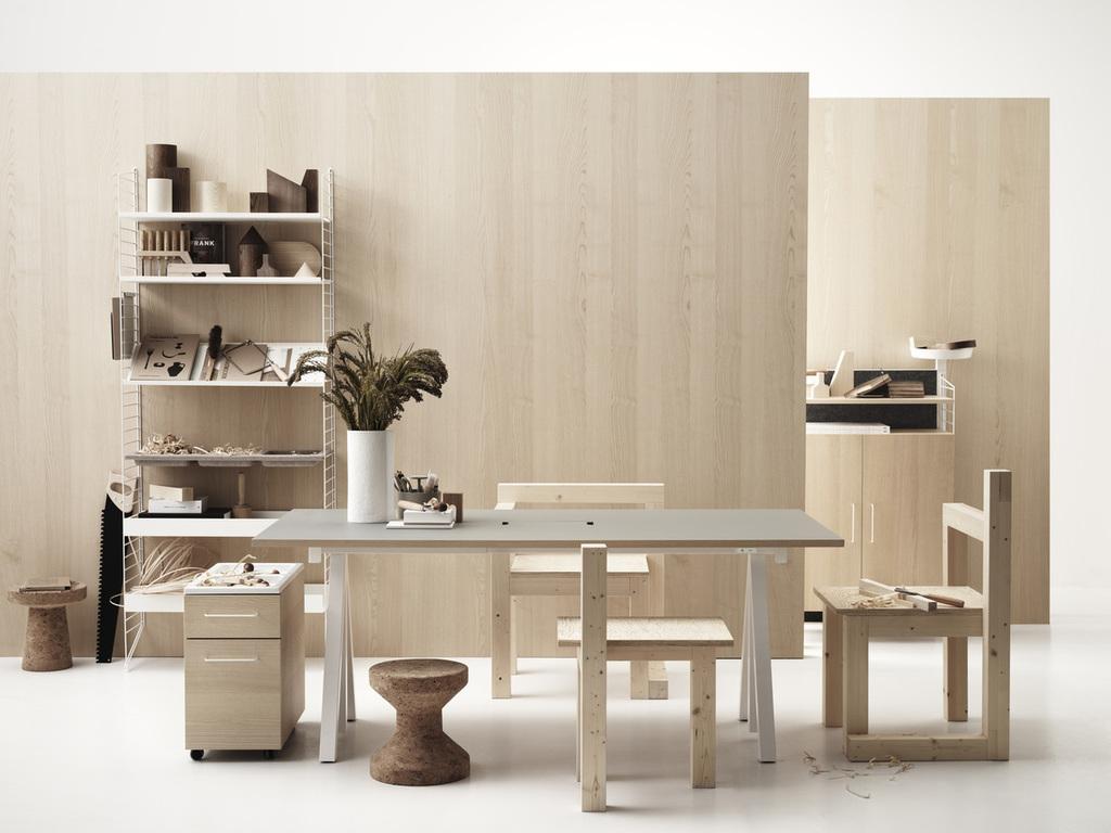 Prateleiras ao fundo. Mesa de madeira de jantar com três cadeiras no centro