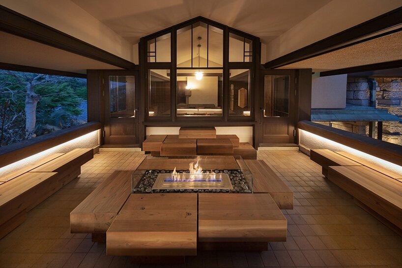 Varanda com bancos feitos de blocos assimétricos de madeira e lareira no centro