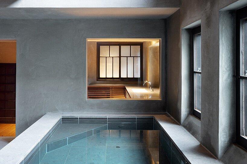 Sala de banho em concreto armado com banheira e duas janelas