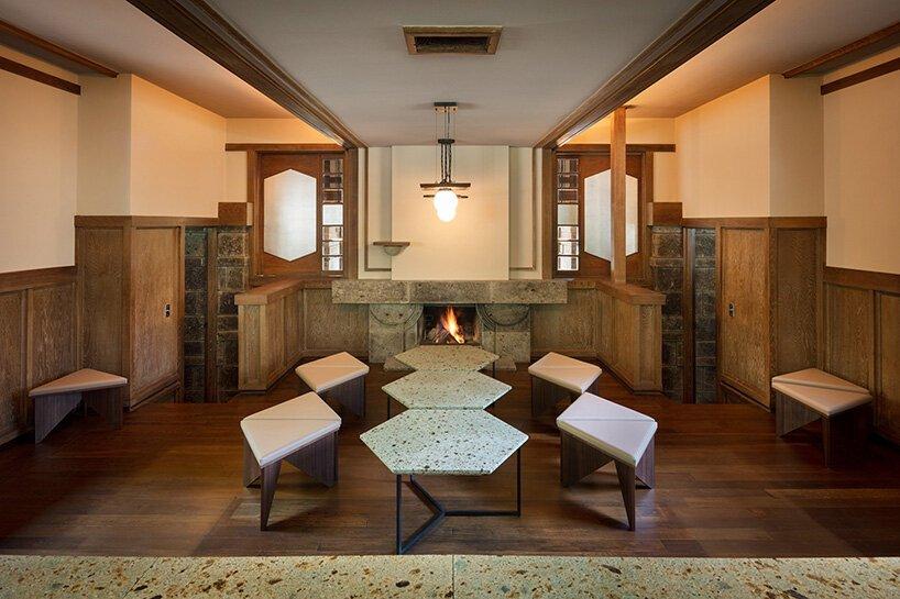 Sala com bancos geométricos e lareira ao fundo