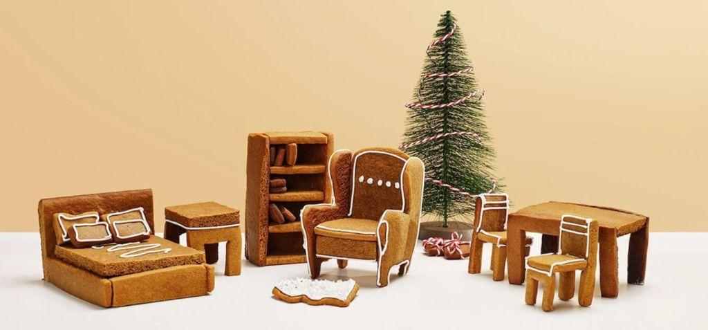 Cama, poltrona, mesa e cadeiras feitas de biscoito. Árvore de Natal ao fundo