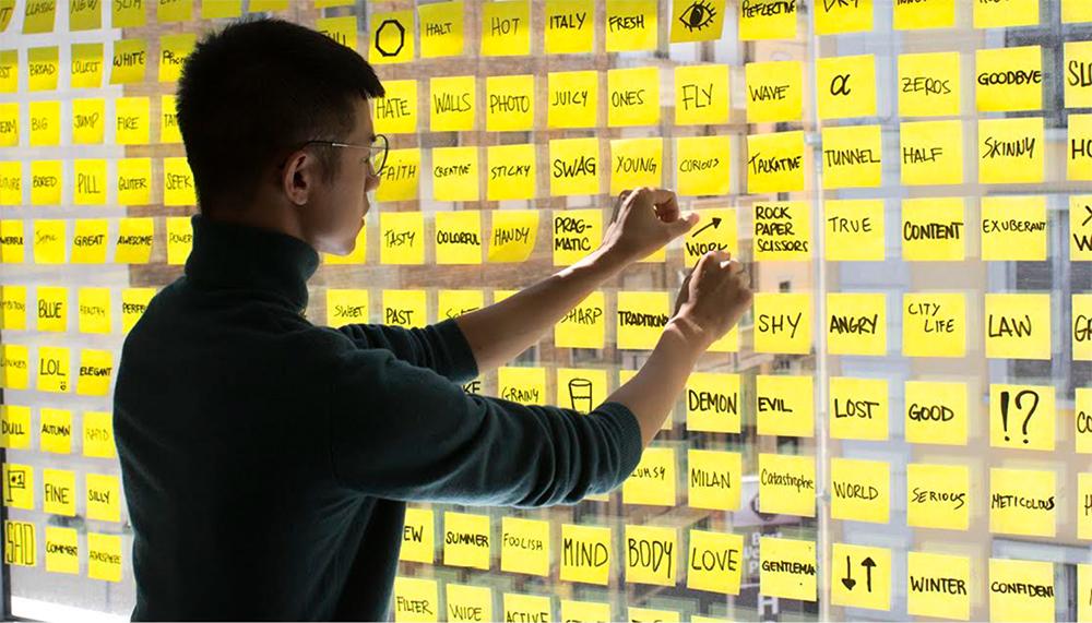 Aluno grudando um post-it amarelo em um painel transparente com outros post-its