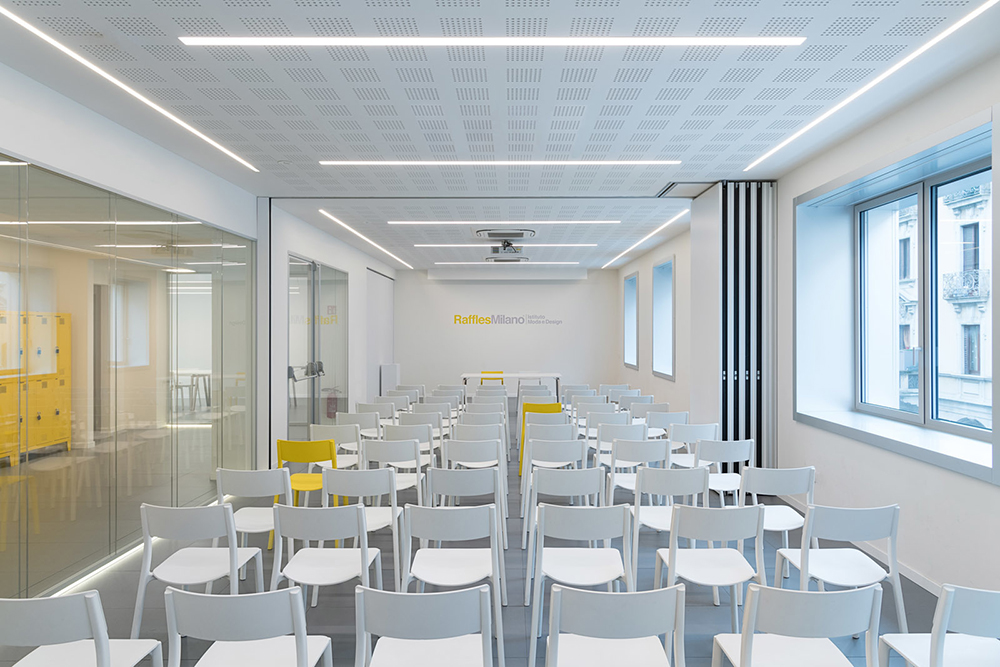 Sala de aula vazia com cadeiras brancas e duas cadeiras amarelas