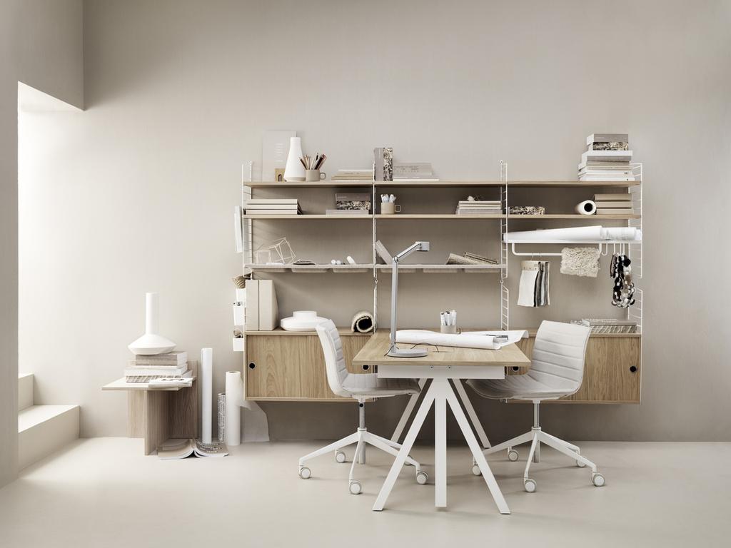 Escritório com prateleiras metálicas brancas e duas cadeiras de escritório brancas, uma de cada lado da mesa que se projeta em ângulo perpendicular das prateleiras