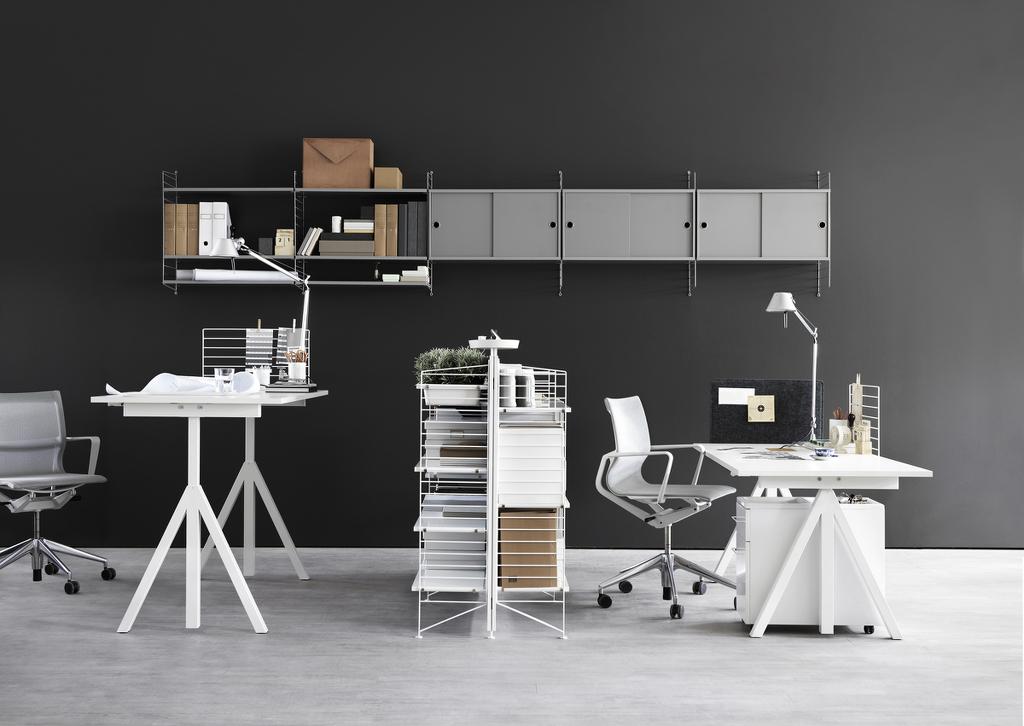Dois conjuntos de mesa e cadeira de escritório dispostos lado à lado, separados por prateleiras metálicas