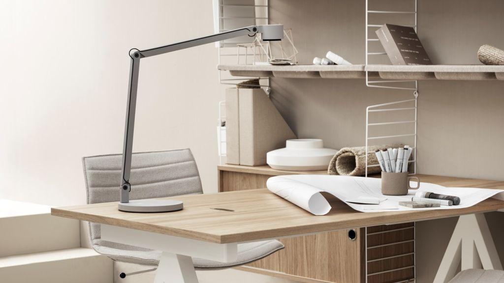 Mesa de escritório branca com tampo em madeira. Cadeira e luminária brancas. Prateleiras ao fundo