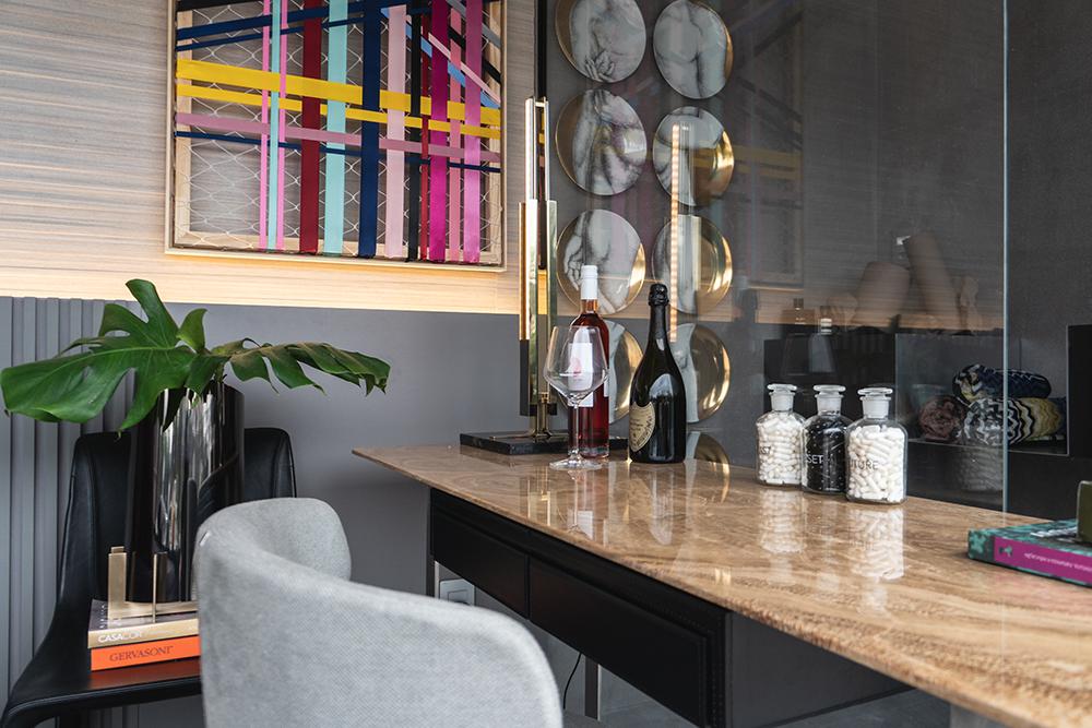 Mesa de trabalho com cadeira cinza e quadro colorido ao fundo