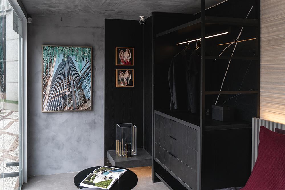 Parede com revestimento de cimento ao fundo e armário de madeira preta