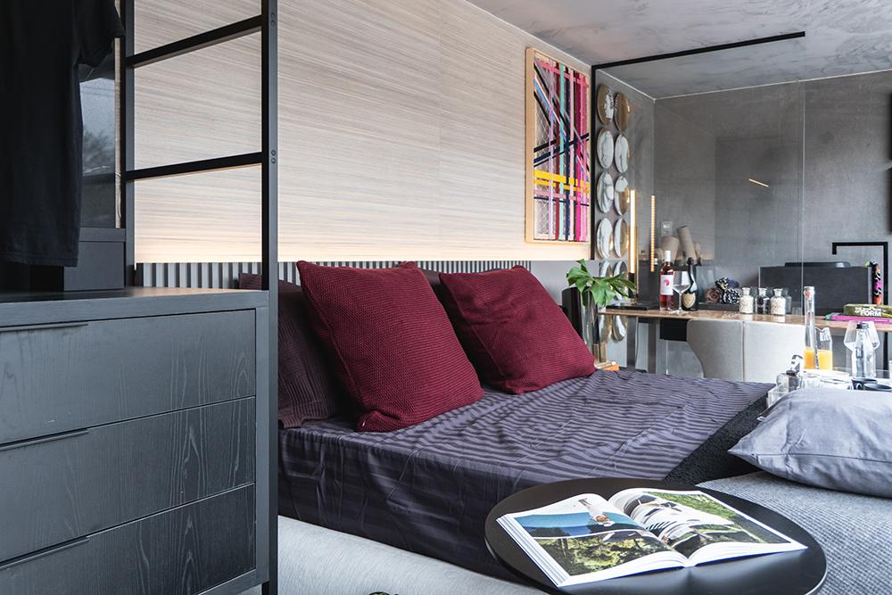 Suíte com cama de casal em primeiro plano, mesa de trabalho e banheiro ao fundo