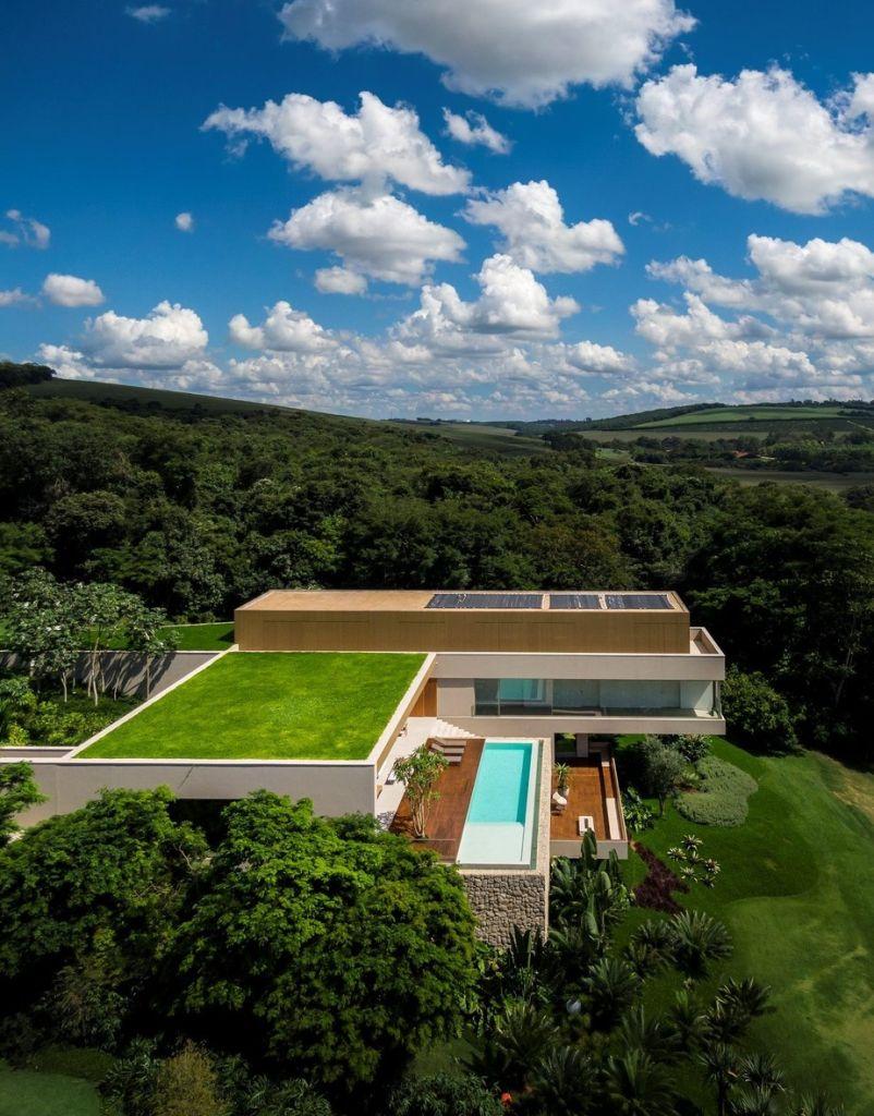 Visão de superior do telhado verde, no nível abaixo, um deck de madeira com uma piscina.
