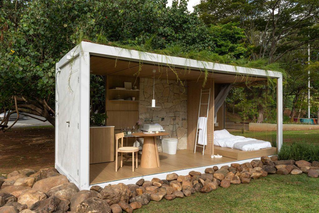 Contêiner branco, com quarto, cozinha e banheiro com mobiliário e peças em madeira. Louças em branco e o telhado verde.