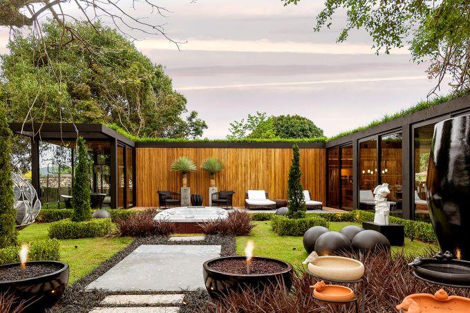 Jardim com caminho de pedra grandes. Ao fundo, a parede de madeira, com parede de vidro a direta, e acima, o telhado verde.