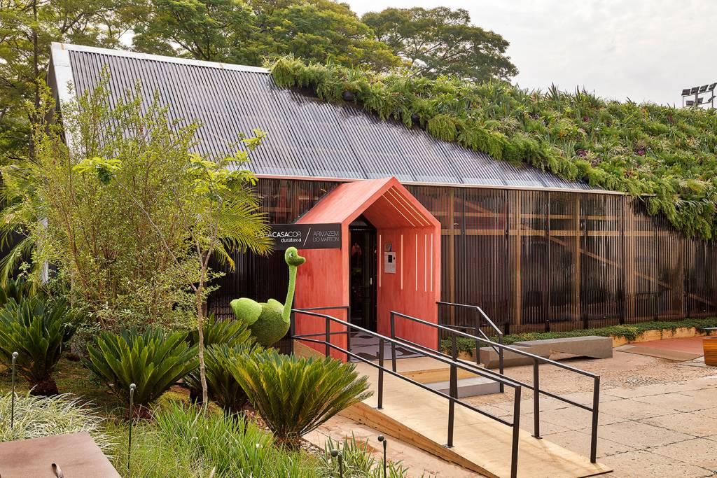 Portal com topo triangular em vermelho. O telhado verde e coberto até a metade em uma linha diagonal. À esquerda da entrada, um avestruz de planta.