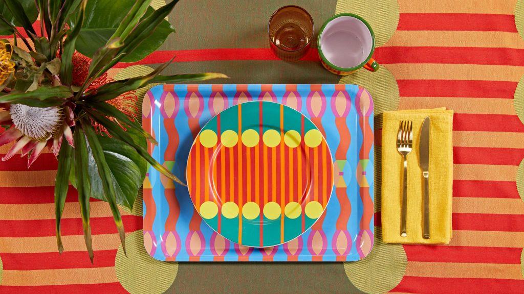 Imagem de prato sobre bandeja, ambos da coleção. Vaso de flor no canto esquerdo superior