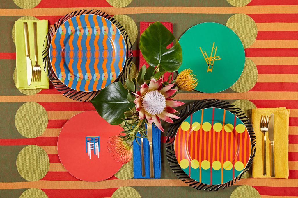 Imagem com quatro pratos sobre toalha da nova coleção e uma flor no centro