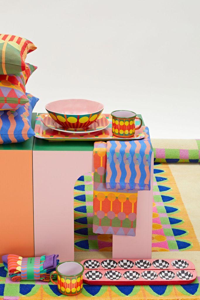 Detalhe do arranjo em cenário branco com todas as peças da coleção, incluindo travesseiros, tapetes, com foco nas canecas e pratos