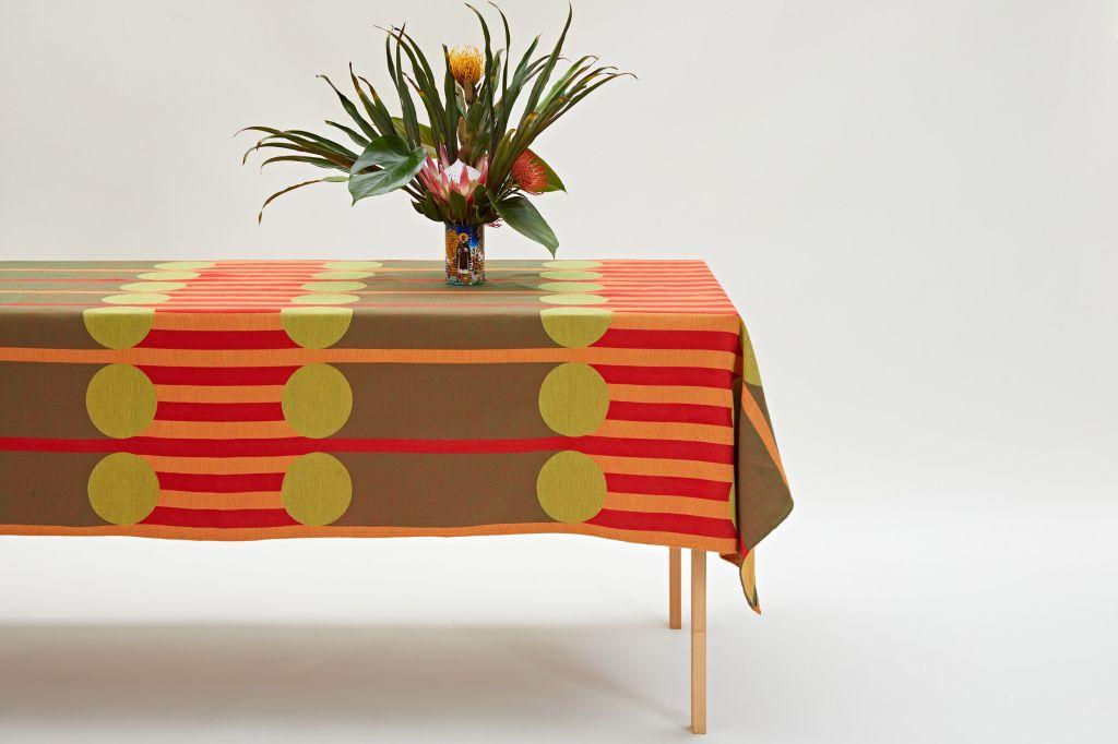 Mesa coberta com toalha da coleção e vaso de flor