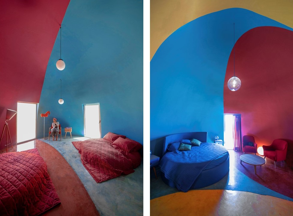 Interior da casa. Paredes coloridas de azul e soa, camas também coloridas