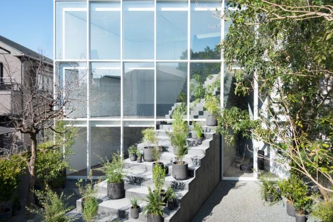 Gigantesca escada teatral que a atravessa diagonalmente, passando pela grande fachada de vidro e subindo até o telhado.