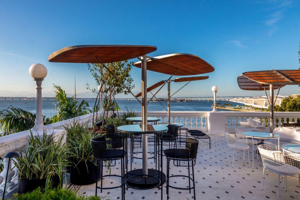 Para-sol BIRD sobre bancos e mesas altas pretas em varanda com mar ao fundo