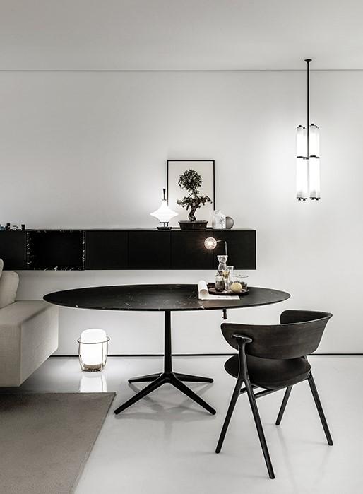 Cadeira Olive preta. Mesa oval preta. Balcão preto ao fundo. Piso e paredes brancas. Luminária à direita