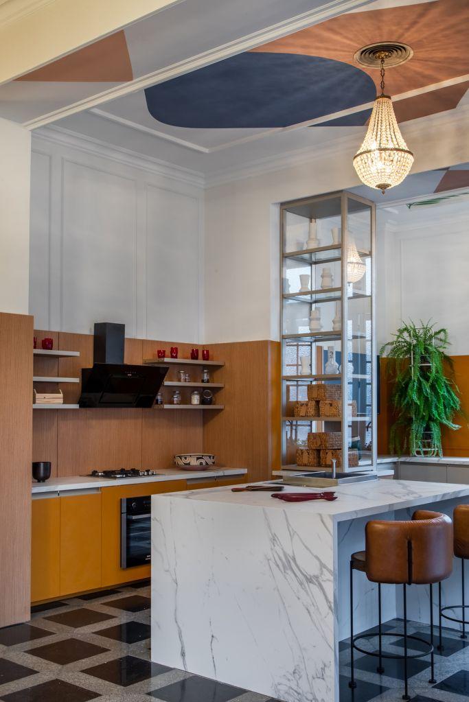 ilha de marmore no centro de uma cozinha em tons de terra e amarelo mostarda