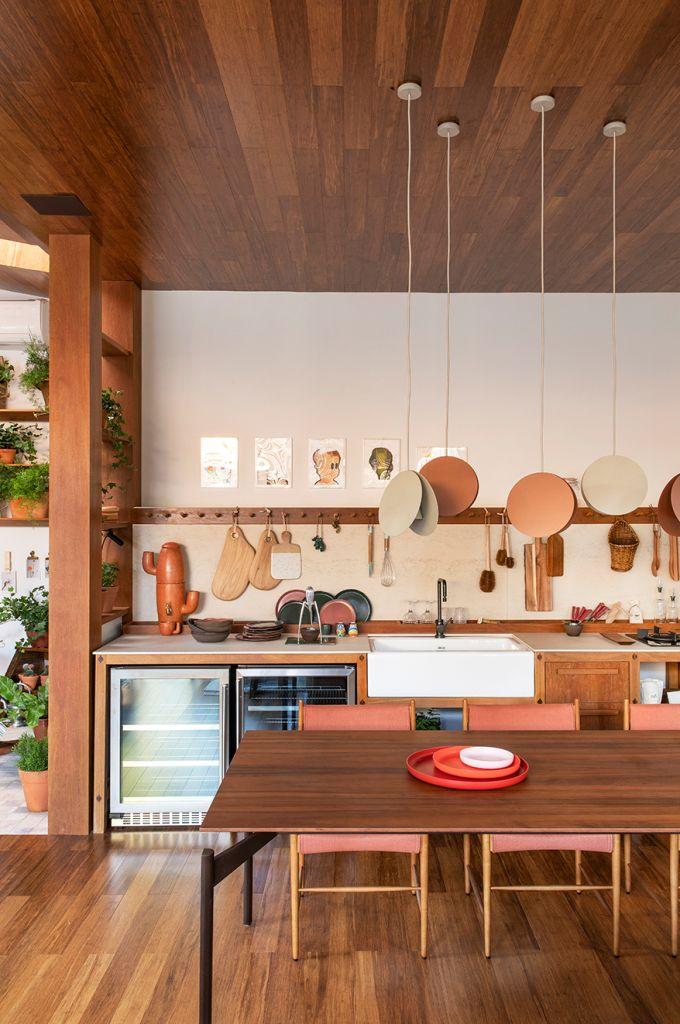 cozinha em tons terrosos com mesa de madeira no centro