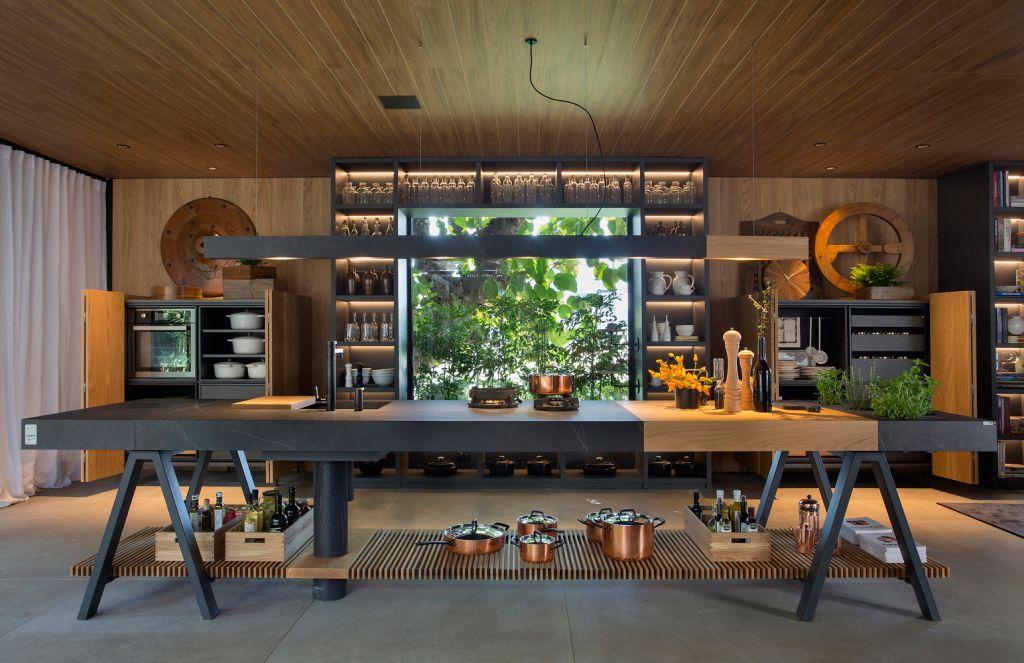 Cozinha com mesa central e nichos distribuídos pela porta