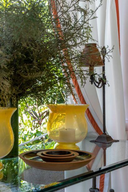 Atrium - CASACOR Rio de Janeiro 2021. Pensado como uma varanda intimista em que se pudesse aproveitar a bela vista para os amplos jardins da residência, o antigo porte-cochère da casa ganhou ambientação casual chic com toques tropicais e o uso de materiais naturais como fibras e palha. Arcos brancos enquadram a natureza em volta.