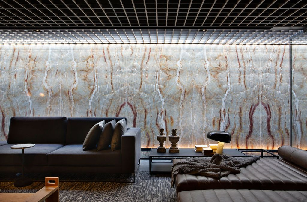 Parede de mármore com sofá na frente em cinza e mesa lateral