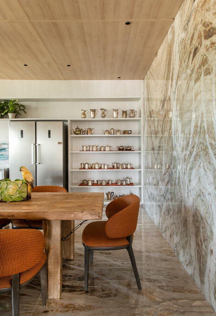 Parede e piso em quartzito claro com mesa de jantar na frente e prateleiras na lateral