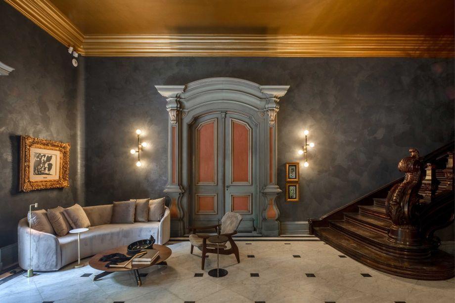 Porta de entrada da casa, o Hall de Entrada de Rodrigo Jorge traz um décor clássico – com direito a paredes grafite e peças dos anos 1950 e 1960. Entre elas, a atemporal poltrona Diz, do mestre Sérgio Rodrigues.